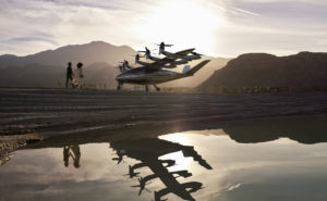 arch aircraft over a body of water with the sun setting in the sky causing a reflection of the aircraft.