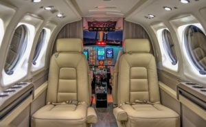 Business Aircraft cabin interior with large lit windows and beige/brown seats.
