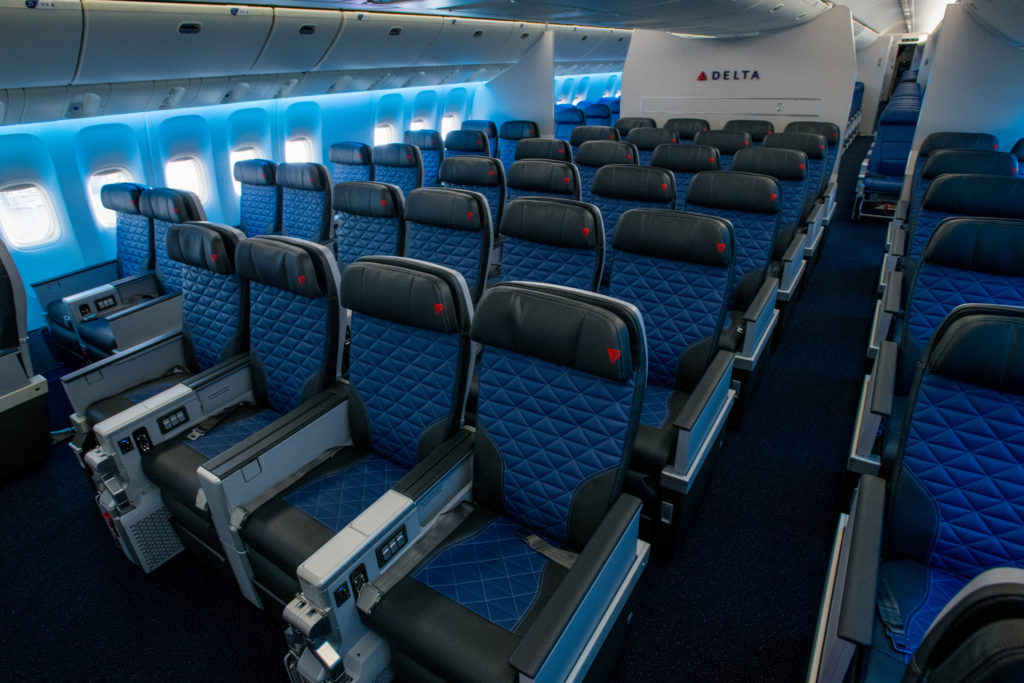 The Collins MiQ seat as seen on board a Delta widebody in premium economy, with the carrier's signature blue seat covers and stitching