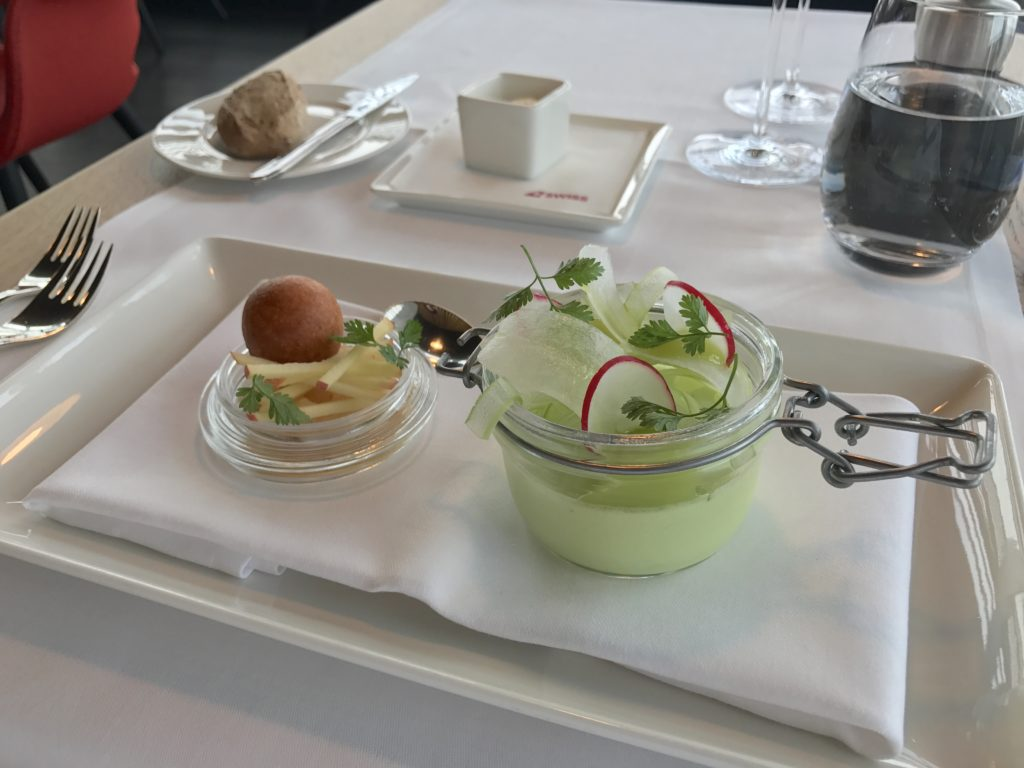 Fun and creative portable menu options in mini-dishes on a tray table in business class.