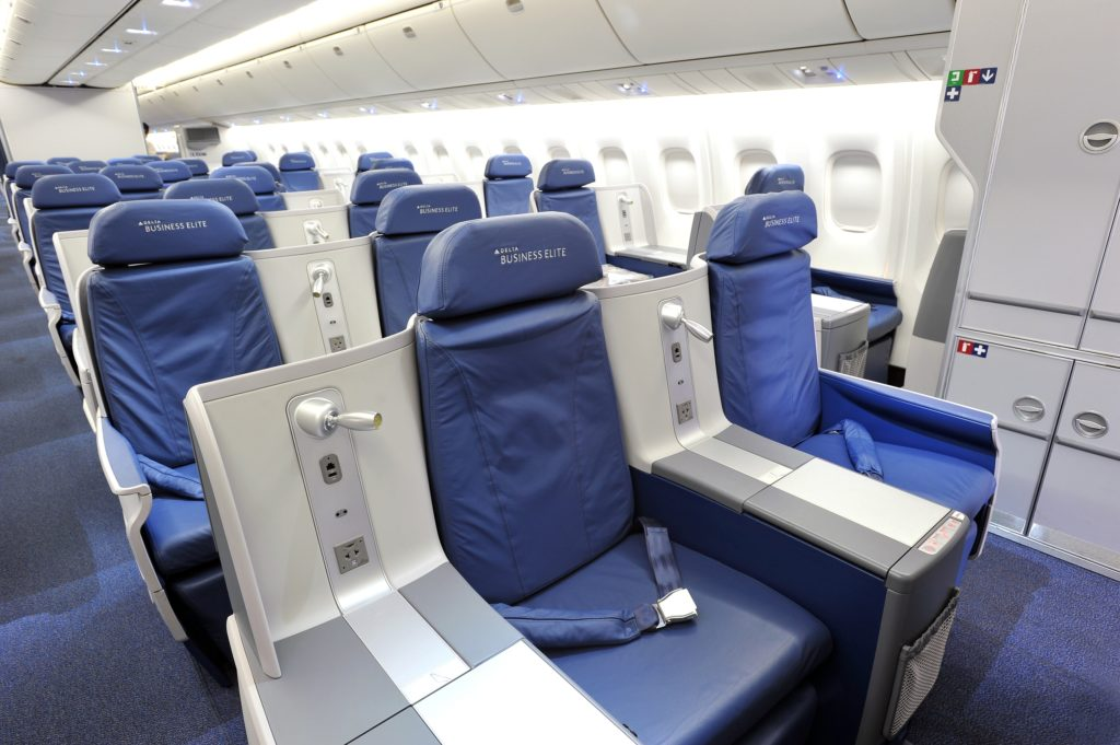 """The """"before"""" image of Delta's aged Thompson Vantage staggered seat in plain blue seat covers, and the word """"BusinessElite"""" on the headrest"""