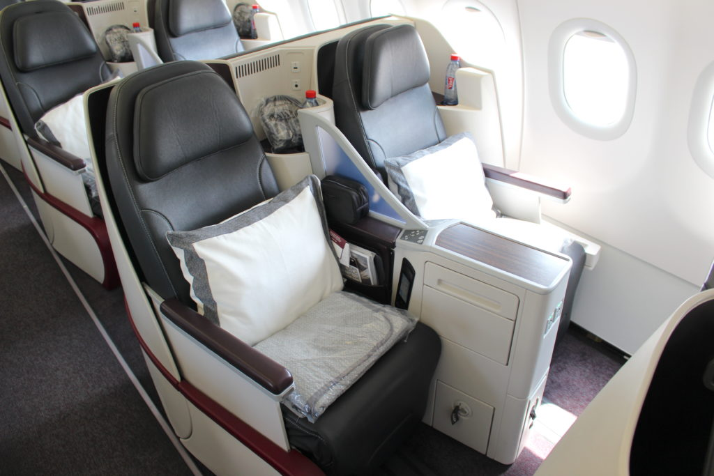 The widely used Diamond seat is pictured, with a dark leather seat covers. Large pillows and blankets are positioned on the seat for passengers