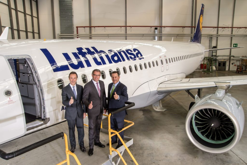 Three executives pose in front of a Lufthansa A320neo, with their thumbs up.