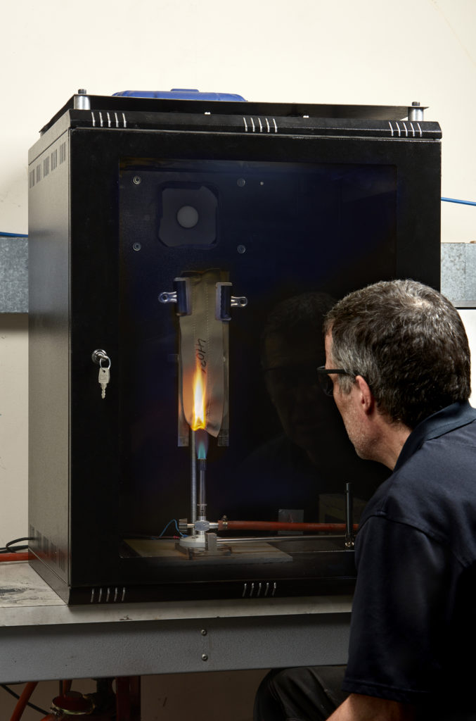 A piece of composite undergoes flam testing in an enclosed black box. A man is peering into the small window on the box, with a flame seen inside