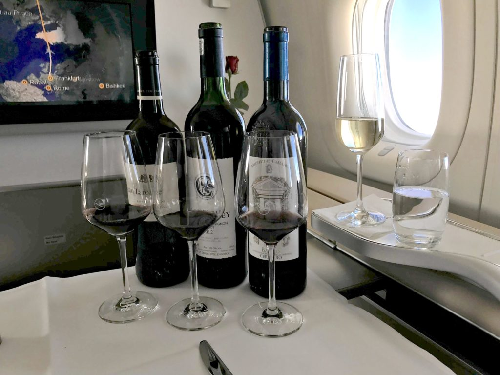 Three bottles of wine, and accompanying glasses, sit atop a tray table in business class. A glass of champers is also in view.
