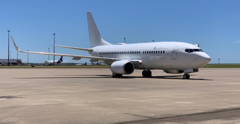 A parked Hillwood Airways 737, in all white, and parked. The aircraft is fitted with the GDC terminal inclusive of ThinKom Ka antenna