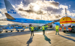 A KLM 737 in the carrier's signature blue livery sits beside a yellow Shell truck at the gate. A glorious sky is in the background, with clouds and sun streaming through