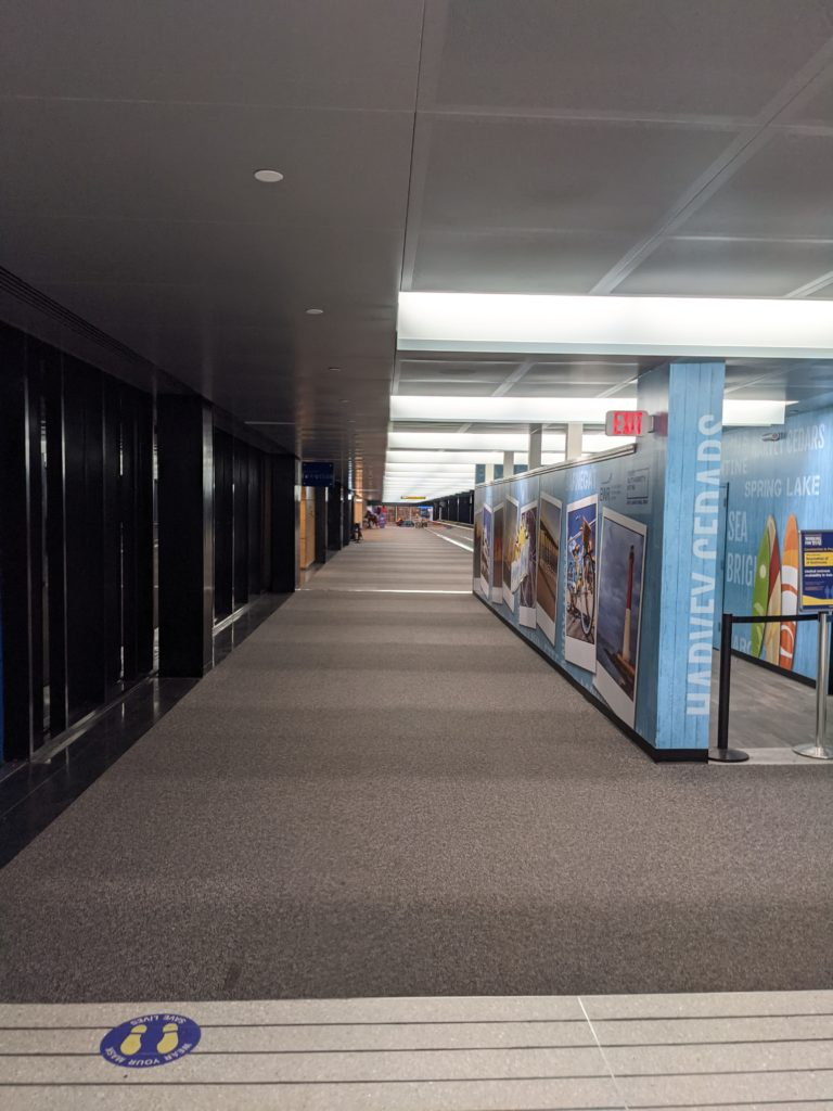 A deserted Terminal B at Newark International Airport. In view is a long, carpeted hallway with no passengers in sight