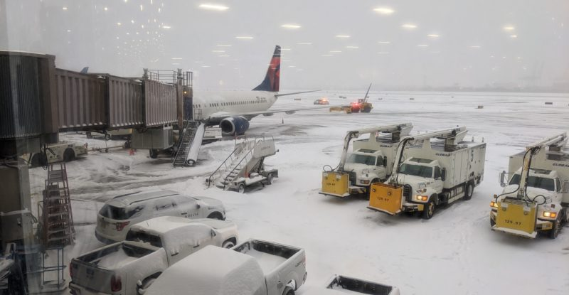 A snowy apron at EWR, with a Delta aircraft parked at the gate, and deicing trucks.