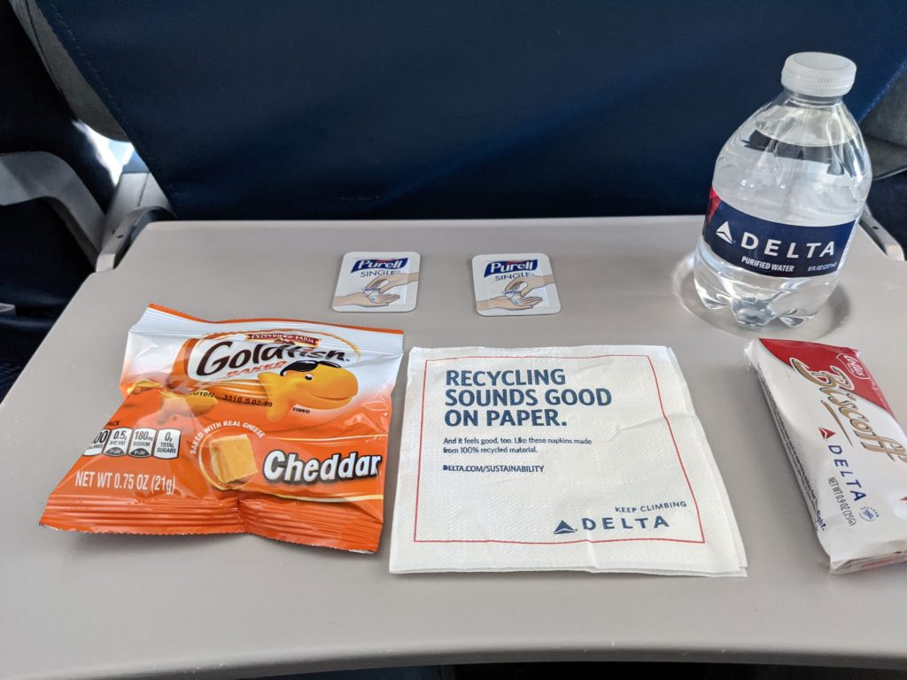 Delta's CareStandard snack pack included cheddar cheese Goldfish, a bottle of water, Biscoff cookies, and hand sanitizer wipes. All of these items are laid out by the author on the tray table.