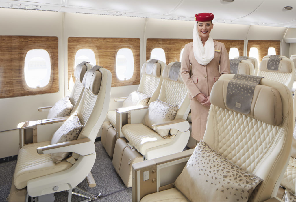 Emirates' sparkling new premium economy seats on board, dressed with cream seat covers and beige headrests, plus beige pillows on the seats