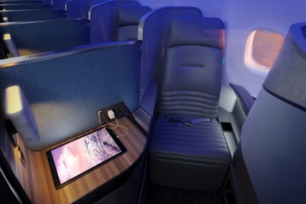 A deep blue stitched fabric covers the Mint suite. Devices are plugged in and lay upon the ample side-table in the suite