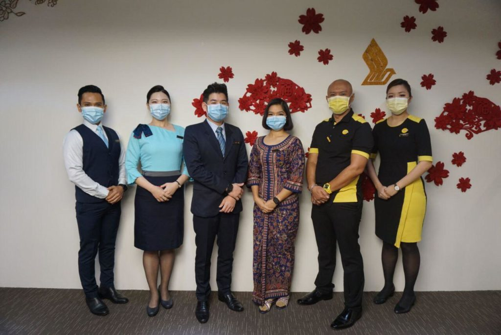 Some of the SIA cabin crew and pilots, in masks, who have received the COVID-19 vaccine