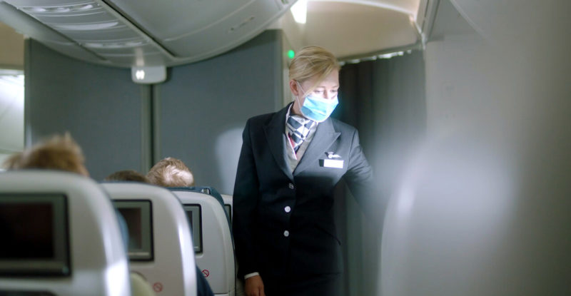 British Airways flight attendant with a mask on standing in the aircraft aisle.