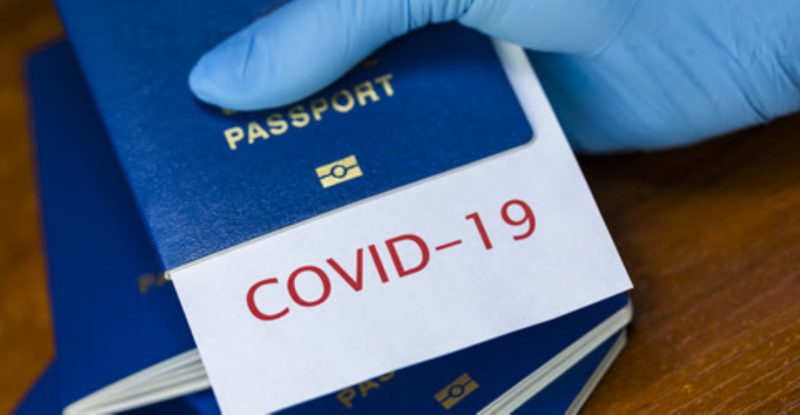 Man holding a passport with COVID-19 sign stamped onto a white paper, immunity passport or risk-free certificate concept, recovered Coronavirus COVID19 patients being issued proof of convalescence