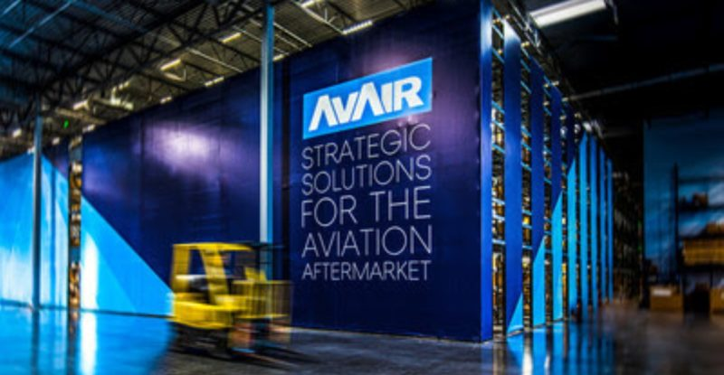 """Blu walls built up in a warehouse with a small forklift passing by. One wall says """"AVAIR Strategic solutions for the aviation aftermarket."""""""