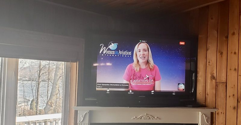 Girls in Aviation host Allison McKay talks to younger viewers on a large living room television