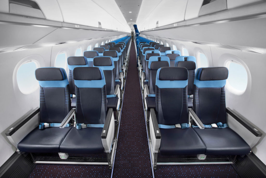 An Embraer E-Jet with 2x2 seating. The seats feature black covers and blue accents