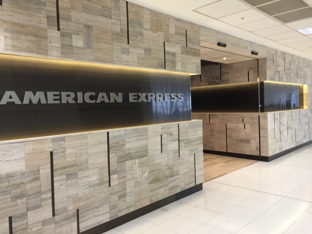 The signage in front of an Amex lounge with big AMERICAN EXPRESS lettering