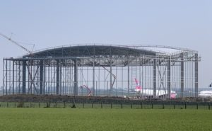 CHR Hanger mid construction shown with aircraft in the background