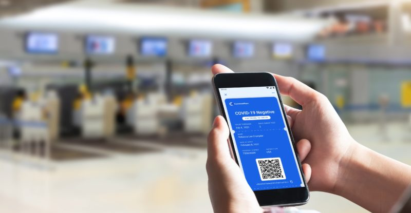 Hands holding up a mobile device in an airport. The device is showing a health passport with a blue sceen and QR Code.