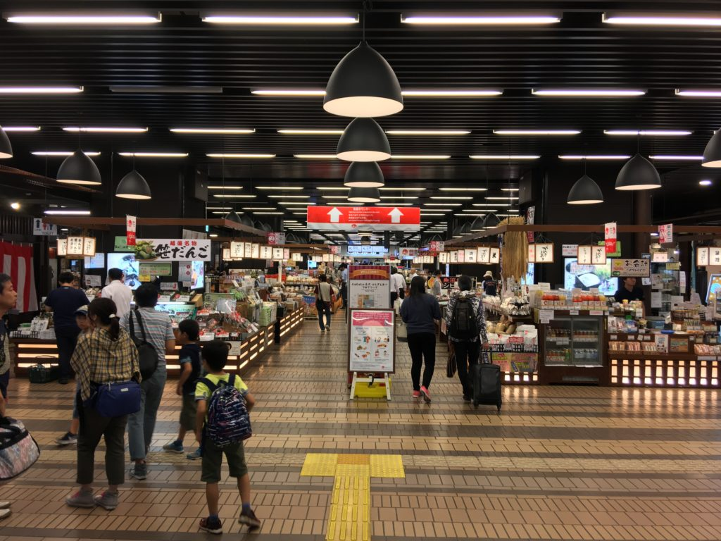 People enjoying a retail space at a Japanese railway station.