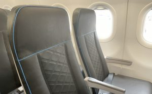Frontier SL3710 seat with grey fabric and sunlight shinning in from an aircraft window.