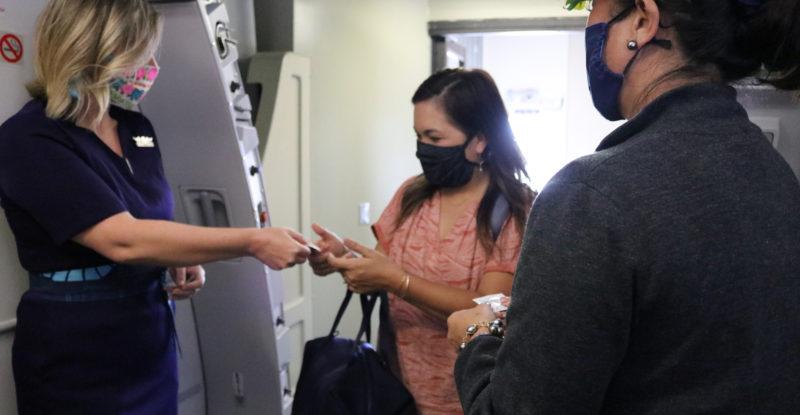 flight attendants of Hawaiian airlines greet passenger in mask.