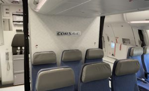CORSAIRbranding displayed on aicraft back panel behind blue and grey seats.