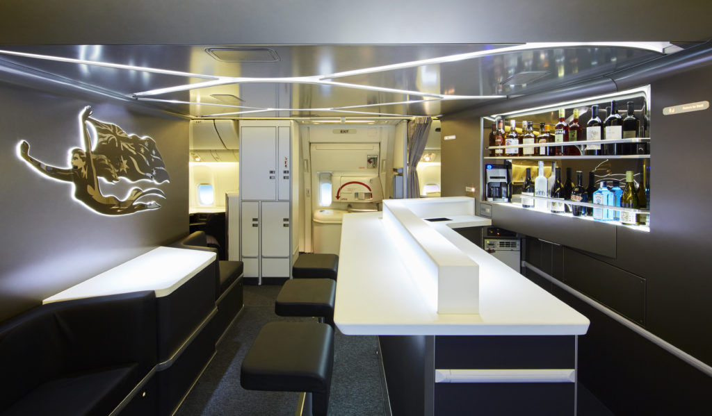 The Virgin Australia bar space, with spectacular lighting and a decorative crest. Two rows of liquor are in view, as well as the long white bar and black stools.