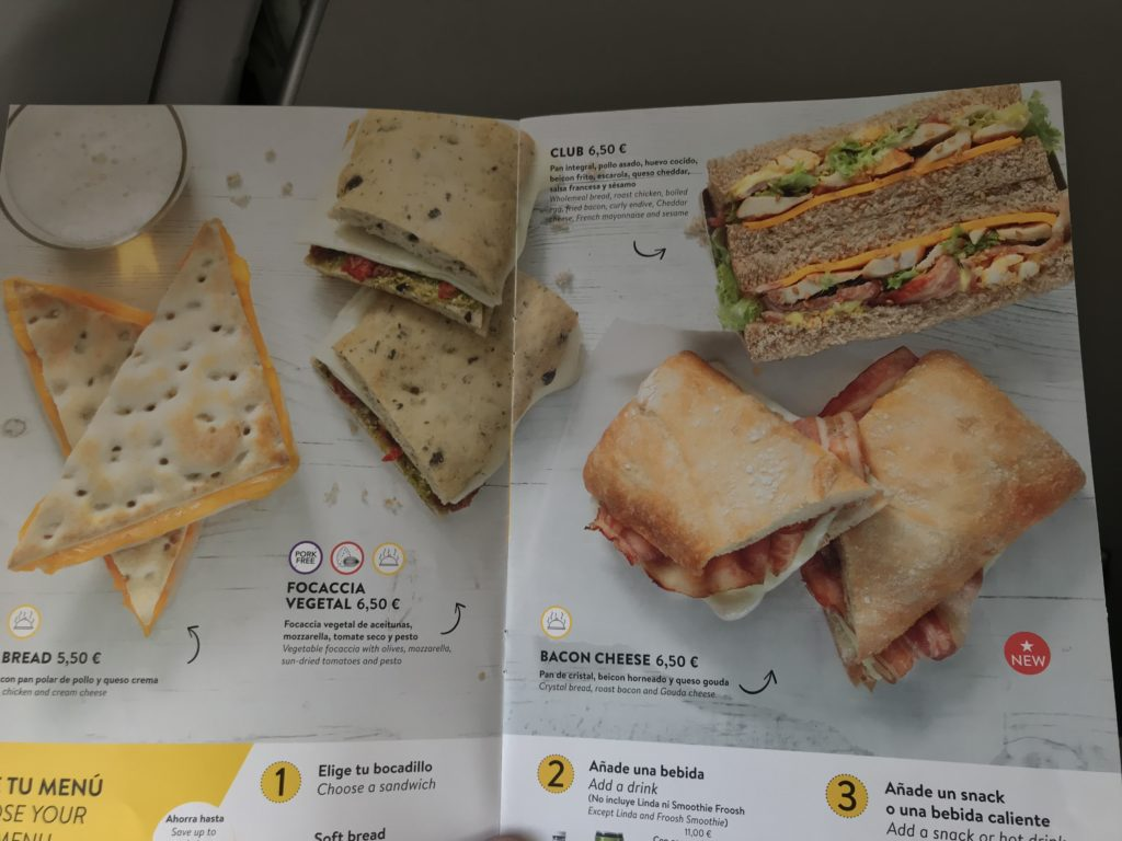 Photo of an inflight menu card displaying various types on sandwiches including Bacon and Cheese, Club and Focaccia Vegetal.