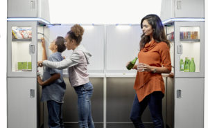 A mother and her two children serving themselves with the M-Flex self service feature. The M-Flex is fully stocked with snacks and beverages.