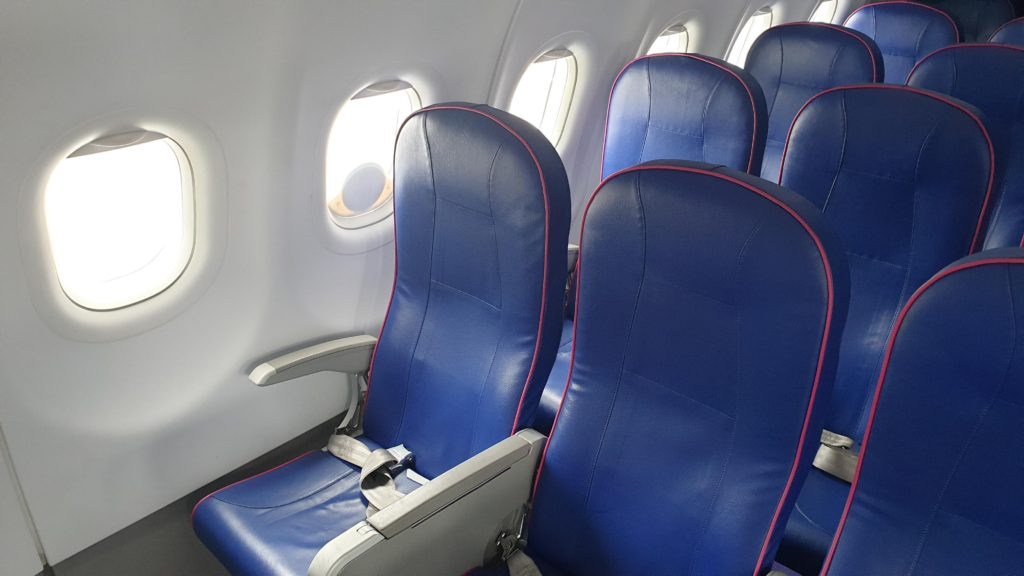 An Iridium antenna attached to an airliner's window, from inside the cabin. The antenna is small and circular. Blue slimline seats are in view.