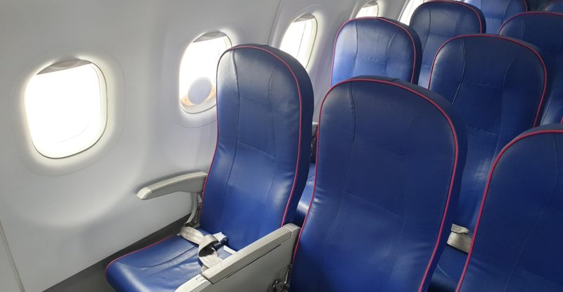 Blue seats on an aircraft. Seats have red trim and are in sets of 3.