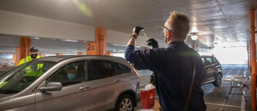 A woman readies to give the COVID-19 vaccine to occupants of a car at SFO Airport