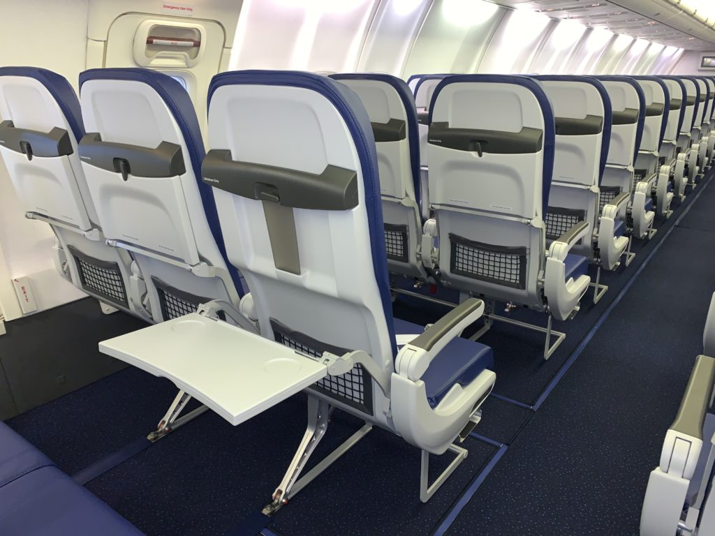 Rows of slimline seats in an aircraft cabin with thermoplastic seatbacks