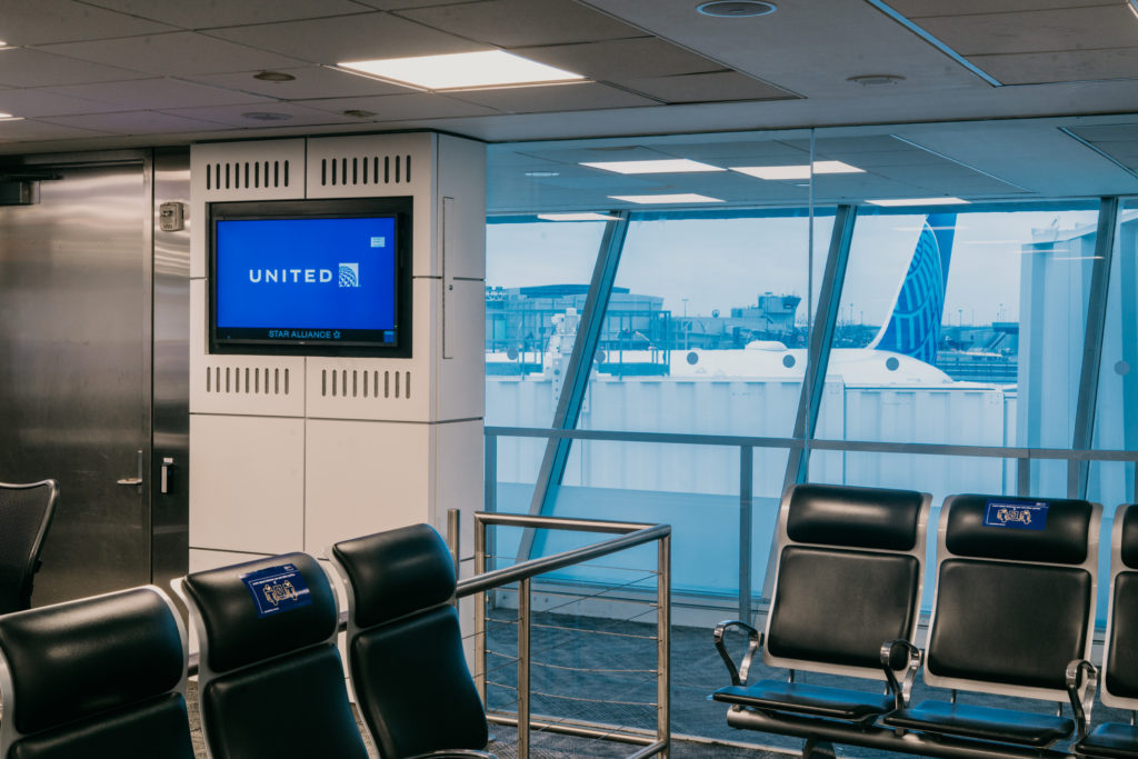 United Airlines gate showing seating, United on the information screen and an aircraft out the window.