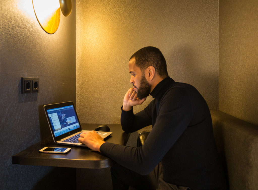 A man sits pensively looking at his computer at a desk in a Star Alliance lounge.