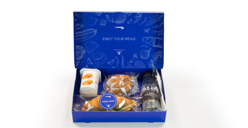 British Airways boxed inflight meal. Displayed in a blue box is a yogurt cup, croissant sandwich, dessert and a bottle of water.