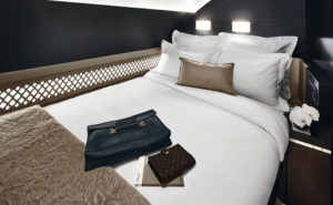 A double bed, as found in Etihad's The Residence, with a thick duvet and pillows, plus amenity kits on the bed.