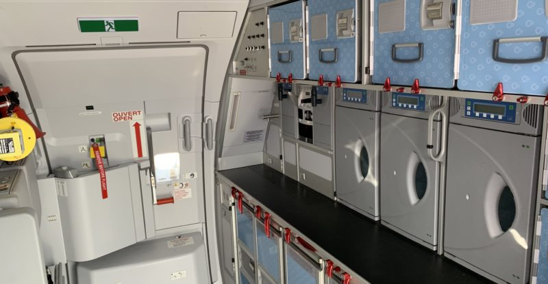An aircraft galley with multiple galley inserts in view, as well as the exit door