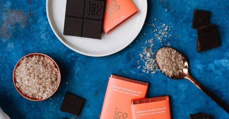 Jcoco smoked sea salt chocolate bars - and a spoon with sea salt - against a blue backdrop.