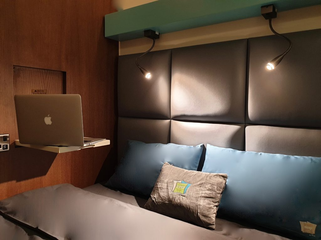 sleep 'n fly cabin DOH displaying a neatly made bed with blue pillows and a small table coming from the wall with an Apple Laptop on it.