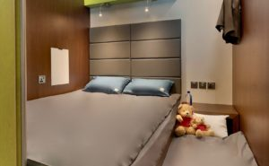 sleep 'n fly cabin DXB displaying a nicely made bed with two blue pillows and a smaller bed along side it with two teddy bears displayed.