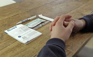 hands folded on a table in front of a laid out COVID-19 test kit.