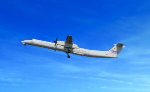 Connect Airlines Q400 in flight with a clear blue sky.