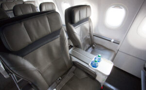 Alaska Airlines' first class seat with dark beige seat covers with black trim. A water bottle is positioned on the side table