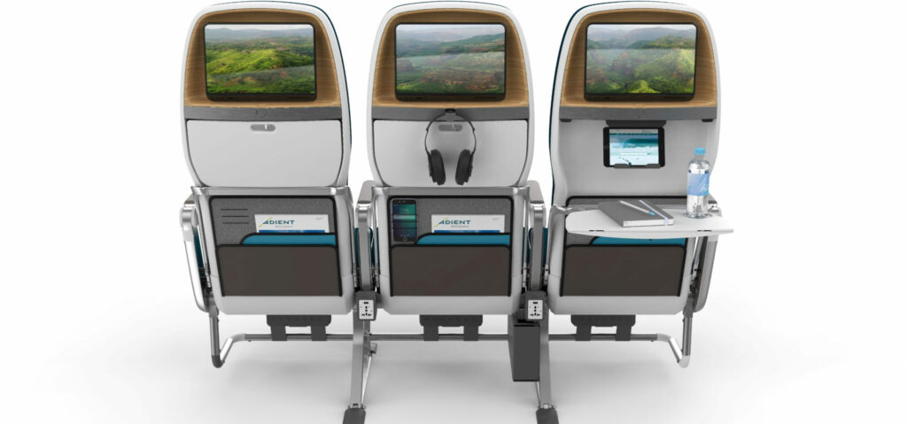Adient Aerospace's Ovation seat in A Boeing 787 model. Showing the back with tray table, headphone holders, tablet holder, IFE Screen and other additions.