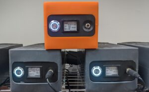 3 AirFi units stacked on top of each other. Two black units on the bottom with an orange unit sitting on top.