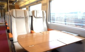 Light beige/cream train seats in pairs with a wood textured table in front of them.